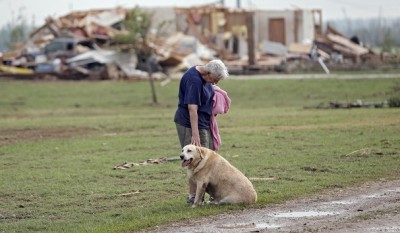 Kay Taylor stands with her dog Bailey in front of her house that was destroyed after the tornado that hit the area near 149th and Drexel on Monday, May 20, 2013 in Oklahoma City, Okla. Photo Credit: AP Photo/ The Oklahoman, Chris Landsberger
