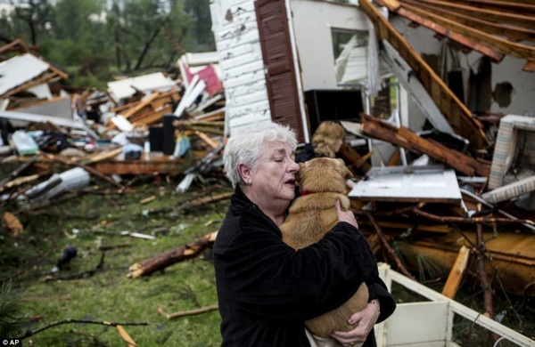 Constance Lambert embraces her dog after finding it alive when returning to her destroyed home in Tupelo, Mississippi, on Monday. Photo Credit: AP
